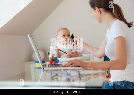 Mother working with little daughter playing at table at home - Stock Photo