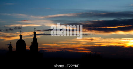 Church in background against sunset with clouds - Stock Photo