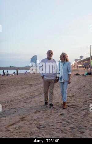Spain, Barcelona, senior couple walking hand in hand on the beach at dusk - Stock Photo