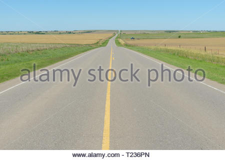 A straight highway runs through wheat fields and agriculture of the Great Plains state of Oklahoma. - Stock Photo