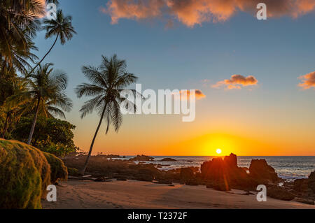 Sunset along the volcanic rock beach of Corcovado national park with a sunbeam by the Pacific Ocean, Osa Peninsula, Costa Rica, Central America. - Stock Photo