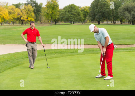 Golfer putting the ball in hole. - Stock Photo