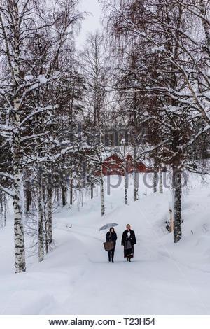 Norwegian women walking through the snow to a wedding ceremony, Plassen Church (kirke), a wooden (stave) church originally built in 1879. It burnt to  - Stock Photo