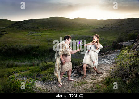 Primitive caveman dressed in animal skin giving flowers to happy cave woman in the mountains - Stock Photo