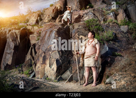 Primitive people dressed in animal skin near ancient cave drawing in the mountains - Stock Photo