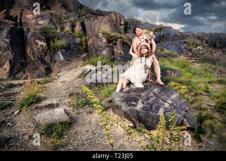 Primitive people dressed in animal skin at the stone with ancient cave drawing in the mountains - Stock Photo