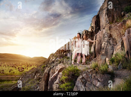 Cave people dressed in animal skin near ancient cave drawing in the mountains at sunset sky background - Stock Photo