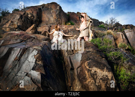 Cave people dressed in animal skin near ancient cave drawing in the rocks - Stock Photo