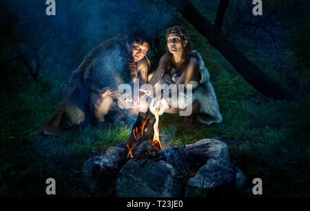 Cave people dressed in animal roast oneself at bonfire in the forest - Stock Photo