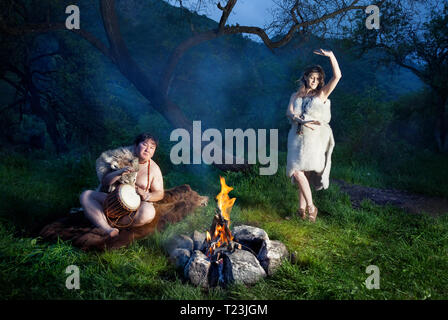 Caveman dressed in wolf skin playing drum and cave woman dancing near bonfire in the forest - Stock Photo