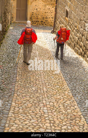 Two pilgrims walking through the cobbled streets of Le Puy en Velay in France. The town is a starting point for many who walk the Santiago de Composte - Stock Photo