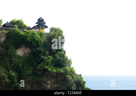 Pura Luhur Uluwatu temple in Bali, Indonesia with cliff with blue sky and sea - Stock Photo