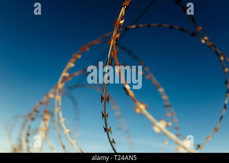 Part of barbed wire fence against blue sky - Stock Photo