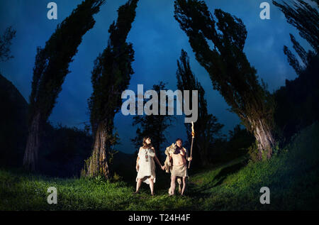 Primitive people dressed in animal with torch light in the dark forest - Stock Photo