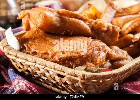 Traditional fish in beer batter and chips served on basket - Stock Photo