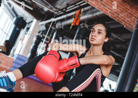 Young girl wearing boxing gloves in gym sporty lifestyle concept sitting on floor looking forward tired bottom view close-up - Stock Photo