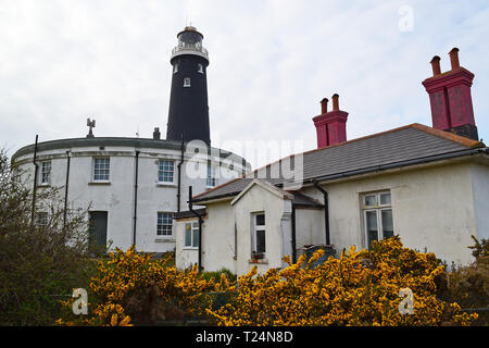 Dungeness Old Lightouse pictured by 18th century lighthouse buildings and Dungeness A decommissioned nuclear power station - Stock Photo