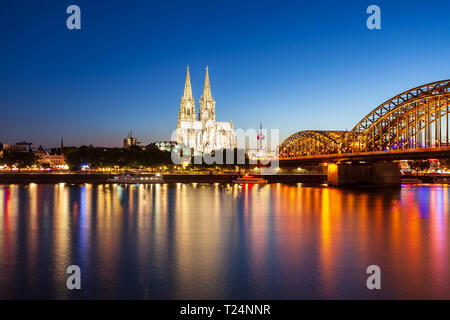 Cologne Cathedral and Hohenzollern Bridge through Rhine river in Cologne, Germany - Stock Photo