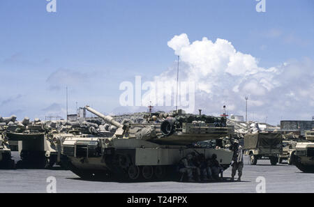 30th October 1993 U.S. Army soldiers shelter from the fierce heat in the shade of their M1A1 Abrams tank of 1st Battalion of the 24th Infantry Division, 1st Battalion of the 64th Armored Regiment. They have just arrived in the new port in Mogadishu, Somalia. The tank is parked next to a couple of M113 APCs. - Stock Photo