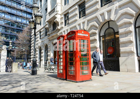 Inoperative Grade II listed red telephone boxes on The Royal Exchange, City of London, UK - Stock Photo