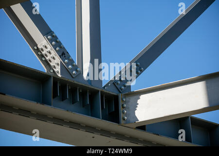 Steel frame of new building in construction - girder joint detail, set against bright blue sky. Shallow depth of field. - Stock Photo
