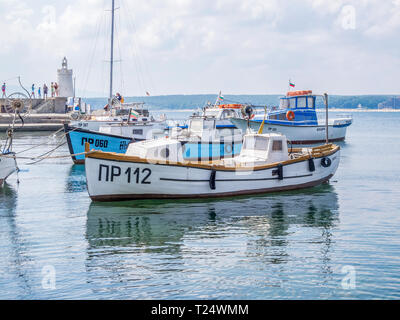 PRIMORSKO, BULGARIA - AUGUST 26, 2011: Port of Primorsko - fishing boats with their reflections on the water surface in the foreground, the small ligh - Stock Photo