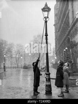 Black and white photograph taken in 1950,  in London, England. It shows a man lighting a gas street lamp, watched by a young girl. and young boy. - Stock Photo