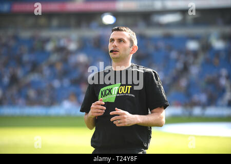 Referee Michael Oliver wearing a Kick it Out shirt before the Premier League match between Brighton & Hove Albion and Southampton at The American Express Community Stadium . 30 March 2019 Editorial use only. No merchandising. For Football images FA and Premier League restrictions apply inc. no internet/mobile usage without FAPL license - for details contact Football Dataco - Stock Photo