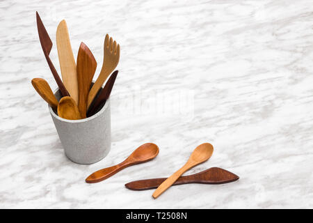 Handcrafted wooden utensils in a concrete cup, on marble background with copy space. - Stock Photo