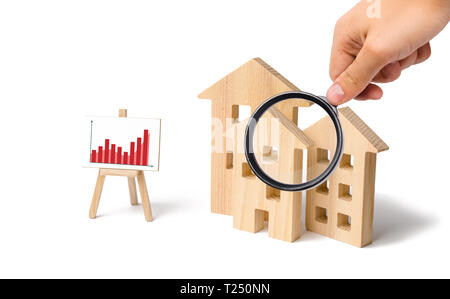 Magnifying glass is looking at the wooden houses with a stand of graphics and information. Growing demand for housing and real estate. Statistics on t - Stock Photo