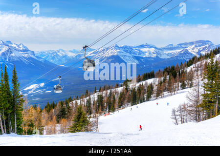 Skiing at Lake Louise in the Canadian Rockies of Alberta, Canada, with cable cars going up the mountains. - Stock Photo