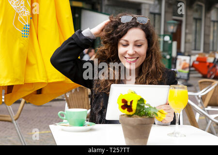 Young girl with long curly hair sitting in a street cafe with coffee and juice in the spring. A beautiful woman uses a tablet to communicate. Street l - Stock Photo