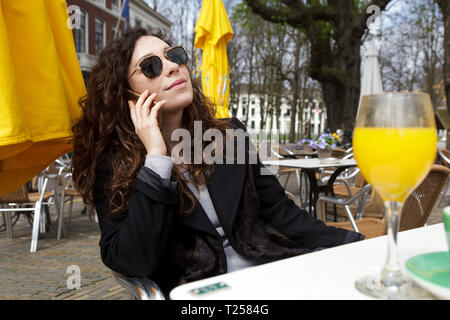 Young girl with long curly hair sitting in a street cafe with and juice in the spring. A beautiful woman uses mobile phone to communicate. Street life - Stock Photo