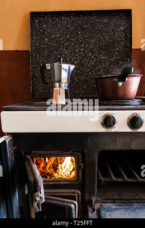 Brewing coffee in a moka pot on a wood fired stove, Bulgaria - Stock Photo
