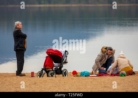 A family enjoying the spring like February weather on the shore of Loch Morlich near Aviemore in the Glenmore Forest Park, Scotland - Stock Photo