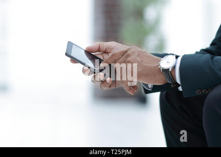 closeup. employee typing SMS on the smartphone - Stock Photo