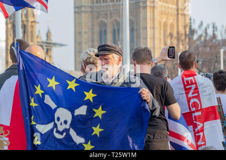 Westminster, London, UK; 29th March 2019; Pro-Brexit Demonstrator Holds Flag During the March to Leave Rally in Parliament Square. Parliament Behind - Stock Photo