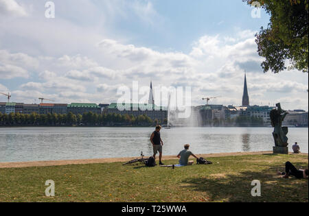Hamburg, Germany - September 04, 2018: A group of people resting on the shore of Alster Lake in downtown district of Hamburg, Germany - Stock Photo