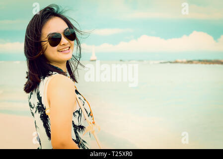 Beautiful woman tourist wearing sunglasse smiling looking at the camera on the beach near the sea at Tarutao island National Park, Satun, Thailand, in - Stock Photo