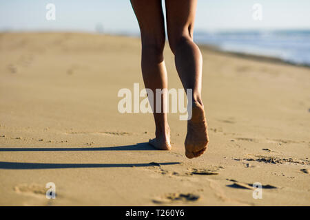Close-up of woman's legs walking in sand on the beach - Stock Photo