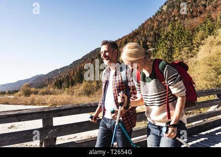 Austria, Alps, happy couple on a hiking trip crossing a bridge
