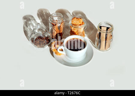 Sticks of sugar and spices in transparent jars with a cup of tea with milk. Cup of coffee and cinnamon into glass jars on white background. - Stock Photo