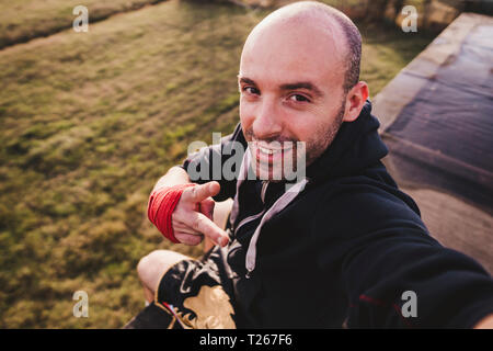 Portrait of smiling boxer sitting on roof terrace - Stock Photo