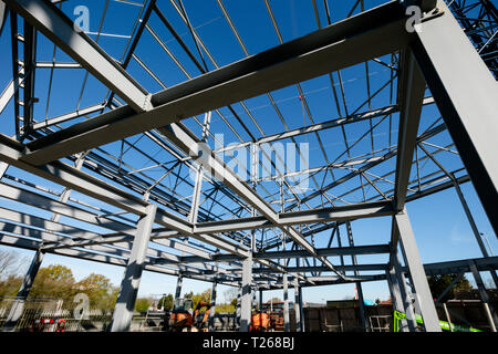 Steel frame of new building in construction set against bright blue sky - roof detail - Stock Photo