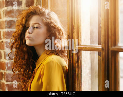 Serious curly ginger girl in the yellow shirt standing back to the window at the loft placement and looking away - Stock Photo