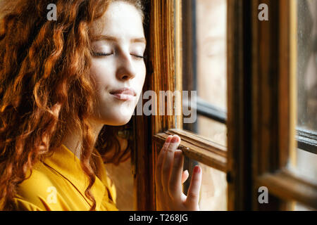Dreamy curly ginger girl in the yellow shirt standing near the window with closed eyes at the loft interior - Stock Photo
