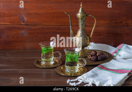 Iftar and Suhoor Ramadan concept ,mentha tea on glass cups and dates on wooden background with an old tea pot - Stock Photo