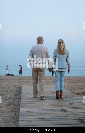 Spain, Barcelona, rear view of senior couple walking hand in hand on the beach at dusk - Stock Photo