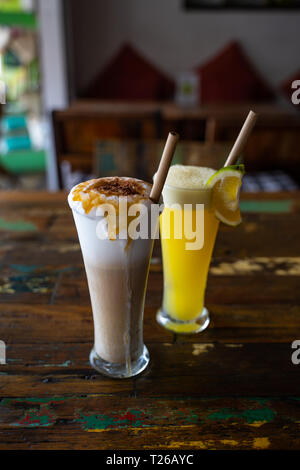 Freshly squeezed orange juice and chocolate milkshake in a tall glasses with a straw on a wooden vintage table in cafe. Copy space - Stock Photo