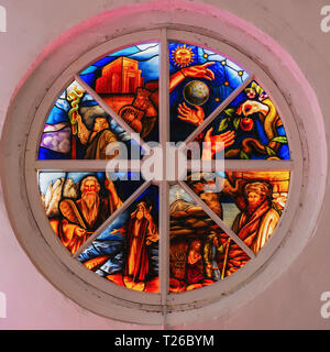 Old round stained glass window in a destroyed in the church, bright colors - Stock Photo